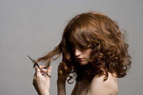 Une femme qui se coupe les cheveux avec des ciseaux
