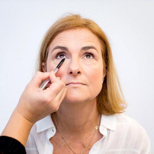 Application d'un fard beige sur le coin interne de l'oeil d'une femme à la peau mature