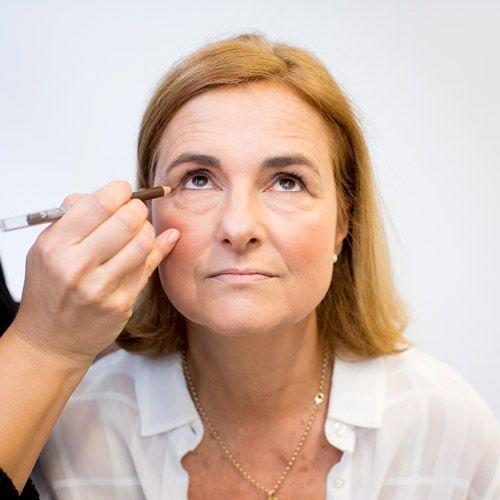 L'application d'un crayon khôl foncé sur l'œil d'une femme à la peau mature