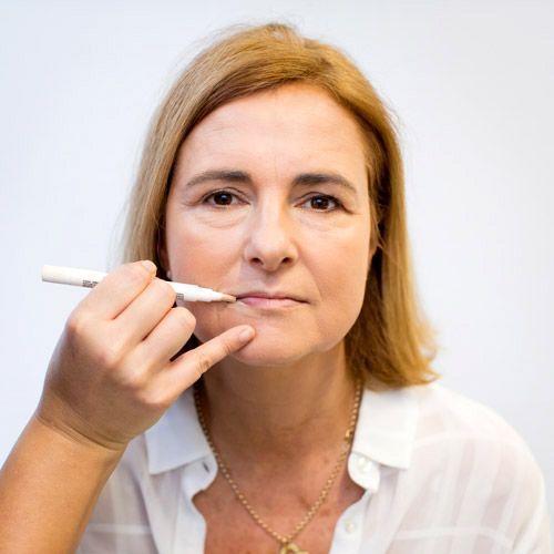 L'application d'un enlumineur sur le contour des lèvres d'une femme à la peau mature