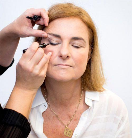 L'application d'un trait de liner sur une femme à la peau mature