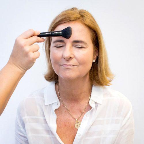 L'application de la poudre fixatrice sur le teint d'une femme mature