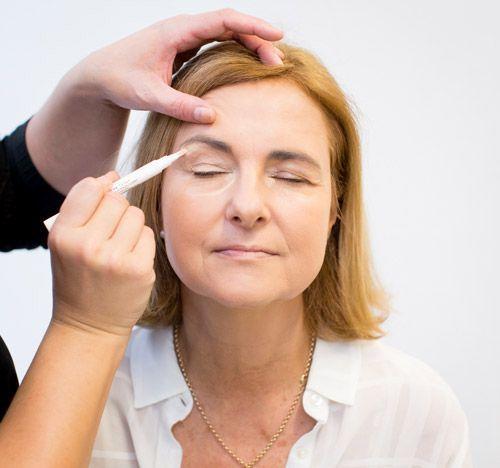 La correction des zones d'ombre avec un enlumineur sur une femme à la peau mature