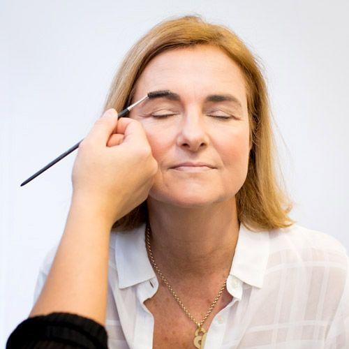 Une femme mature dont on brosse les sourcils vers le haut