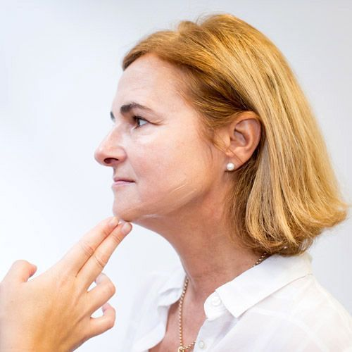 Une femme qui applique de la crème anti-âge