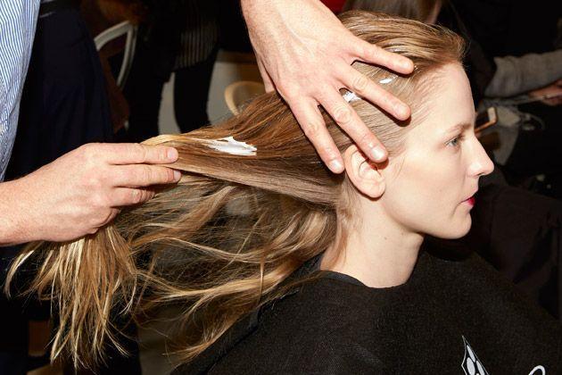 L'application de mousse effet volume sur les cheveux d'un mannequin.