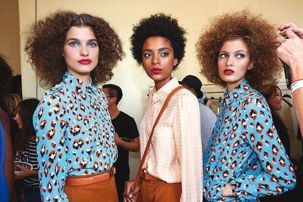 Trois mannequins aux cheveux frisés.