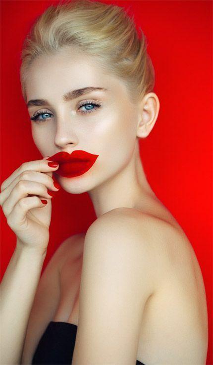 Une jeune femme qui porte un rouge à lèvres rouge.