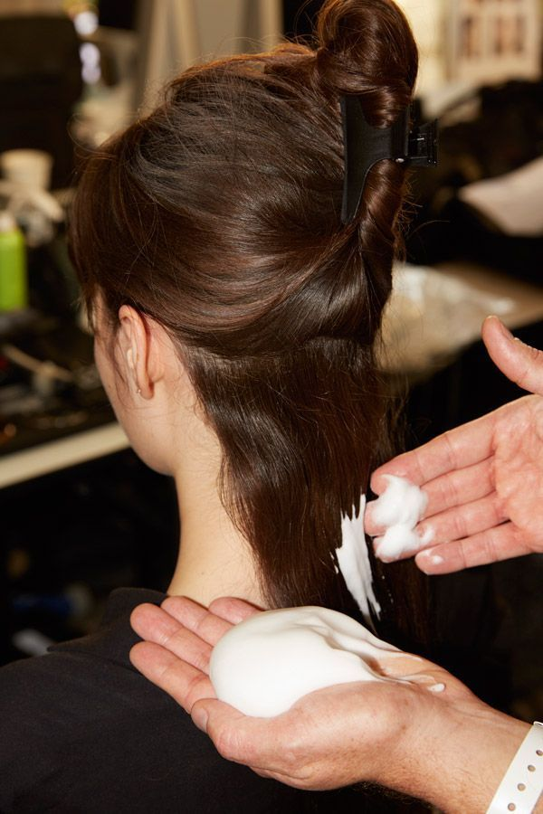 De la mousse coiffante appliquée dans les cheveux.