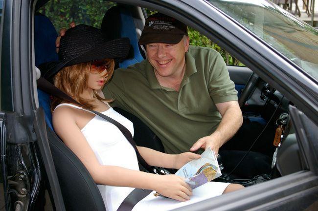 Un homme et sa real doll dans une voiture.