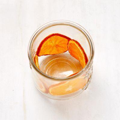 Des rondelles d'orange dans un pot en verre.