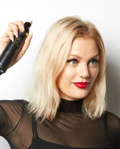 Une femme qui applique du spray thermoprotecteur.