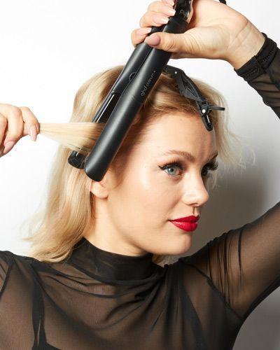 Une femme qui se coiffe avec un fer à lisser.