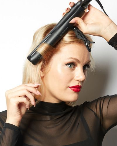 Une femme qui ondule ses cheveux avec un fer à lisser.