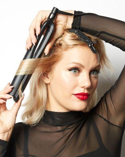 Une femme qu boucle ses cheveux avec un fer à lisser.