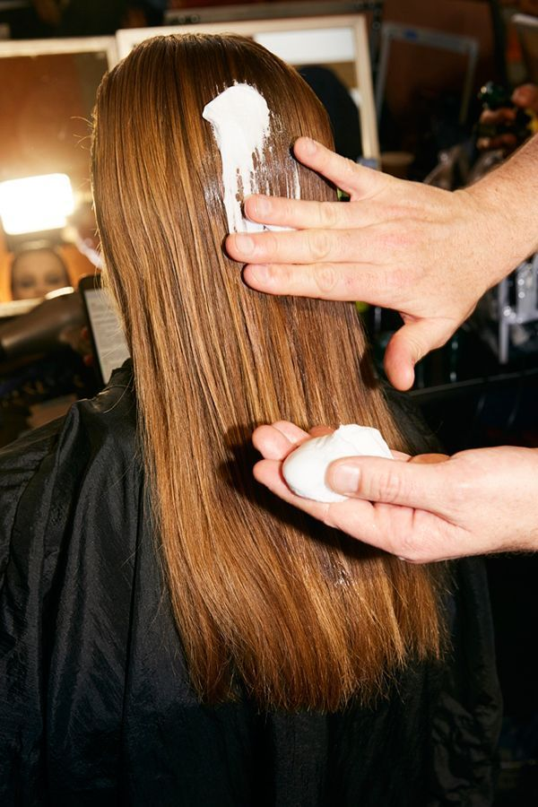 L'application d'une mousse coiffante sur les cheveux.