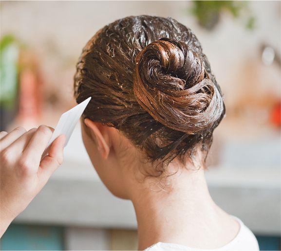 Une femme qui peigne ses cheveux avec un peigne anti-poux.