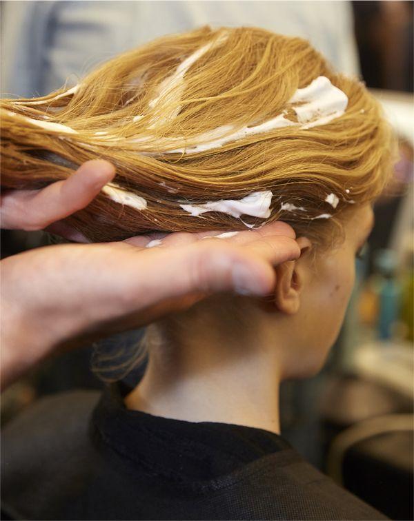L'application d'une mousse coiffante dans les cheveux.