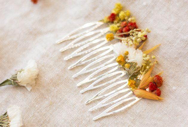Un peigne pour les cheveux avec des fleurs séchées.