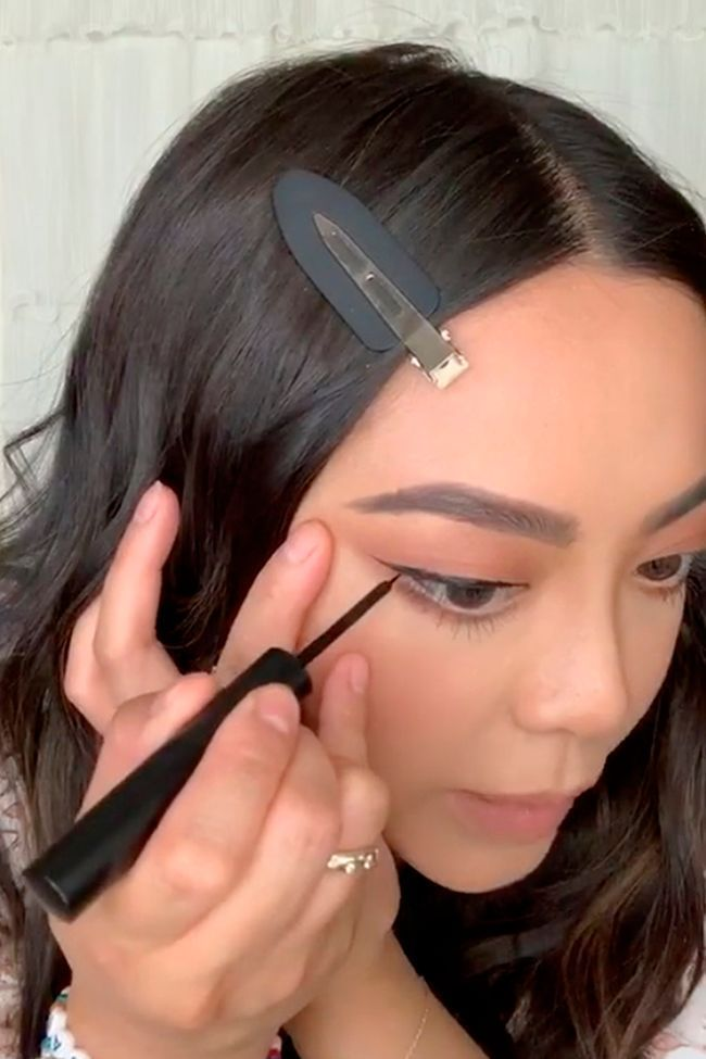 Une femme qui trace un trait d'eye liner magnétique.