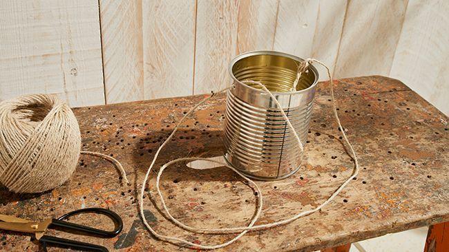 Une boîte de conserve percée pour faire un pot de plantes suspendues.