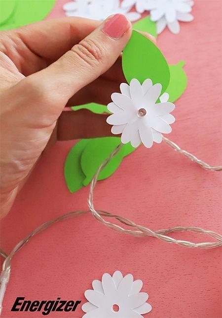 Des fleurs en papier sur une guirlande lumineuse.